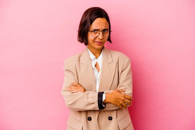 Młody biznes kobieta rasy mieszanej na białym tle na różowym tle podejrzany, niepewny, bada cię.