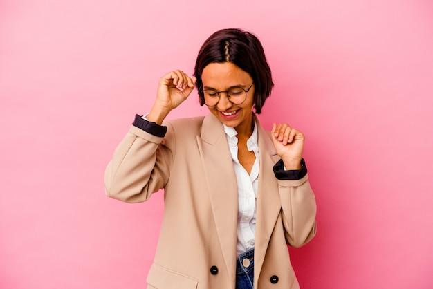 Młody biznes kobieta rasy mieszanej na białym tle na różowym tle świętuje specjalny dzień, skacze i podnosi ramiona z energią.