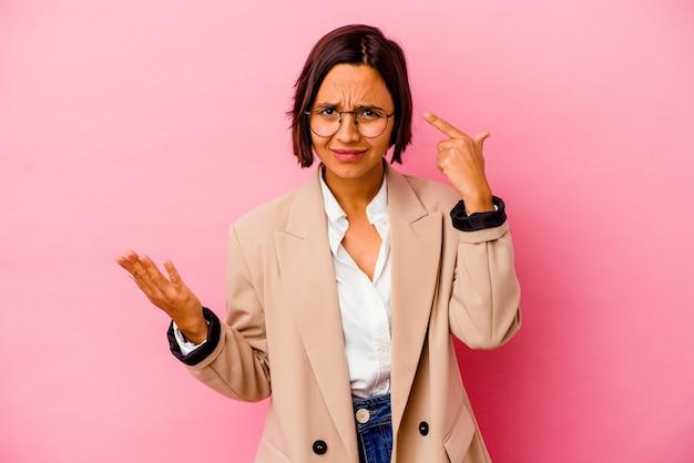 Młody biznes kobieta rasy mieszanej na białym tle na różowym tle trzymając i pokazując produkt pod ręką.