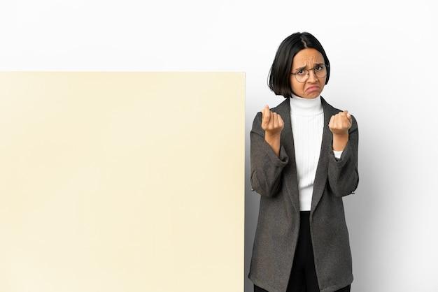 Młody biznes kobieta rasy mieszanej z dużym sztandarem na białym tle, czyniąc gest pieniędzy, ale jest zrujnowany