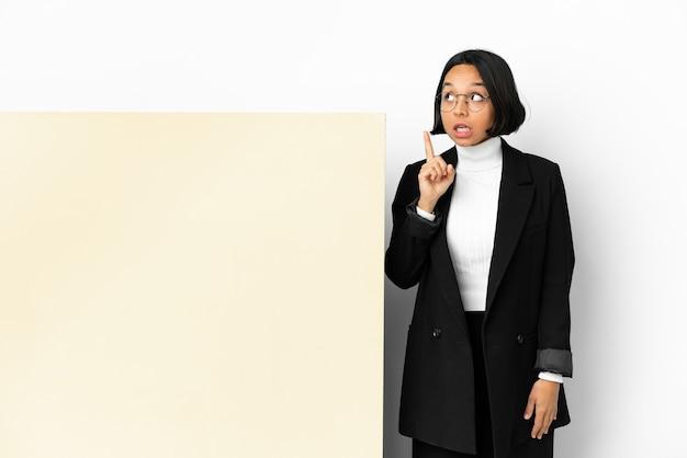 Młody biznes kobieta rasy mieszanej z dużym sztandarem na białym tle myśląc pomysł wskazując palcem w górę