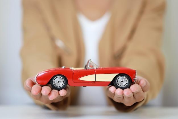 Młody biznes kobieta ręce siedzi trzymając i chroniąc model samochodu na białym stole.