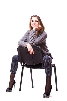 Młody biznes kobieta siedzi na krześle na białym tle na białej ścianie
