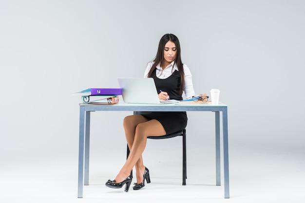 Młody biznes kobieta siedzi przy stole roboczym, pracując na papierach i laptopie na szarym tle