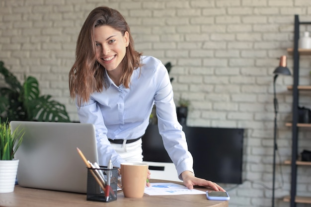 Młody biznes kobieta stojąca w jej domowym biurze pisania notatek.