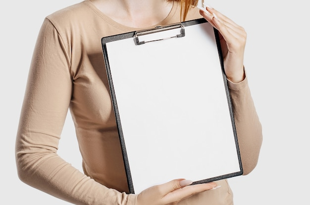 Młody biznes kobieta trzyma schowek z makiety puste miejsce na białym tle na szarym tle.