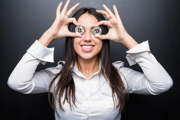 Młody biznes kobieta uśmiech obejmuje oczy z bitcoin na białym tle na czarnej ścianie