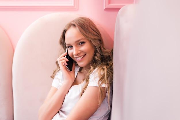 Młody biznes kobieta w szarej sukience siedzi przy stole w kawiarni, rozmawiając przez telefon oncell podczas robienia notatek w notatniku. na stole laptop i filiżankę kawy. uczeń uczący się online. freelancer pracujący online.