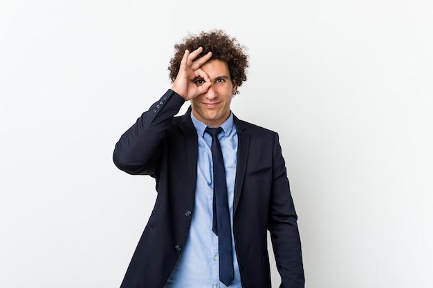 Młody biznes kręcone mężczyzna przeciwko białym podekscytowany utrzymując ok gest na oko.