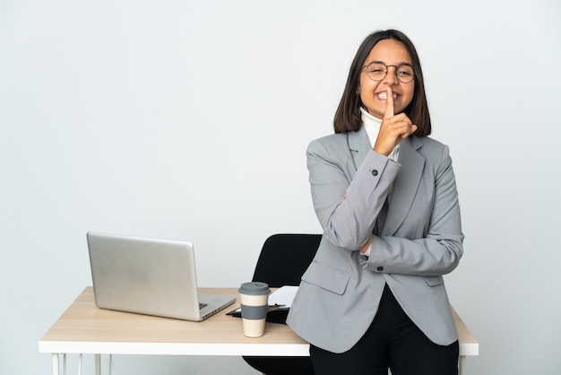 Młody biznes łaciński kobieta pracująca w biurze na białym tle na białej ścianie przedstawiający znak gestu ciszy wkładając palec do ust