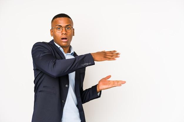 Młody biznes łacińskiej mężczyzna na białej ścianie zszokowany i zaskoczony, trzymając pustą przestrzeń między rękami.