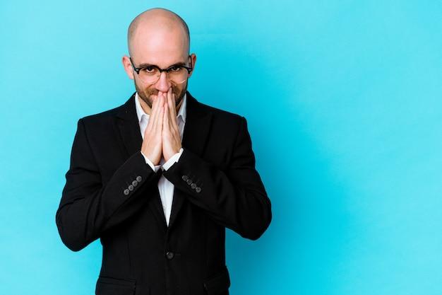 Młody biznes łysy mężczyzna na białym tle na niebieskiej ścianie tworząc plan w głowie, tworząc pomysł