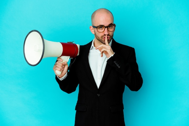 Młody biznes łysy mężczyzna trzyma megafon na białym tle, zachowując tajemnicę lub prosząc o ciszę.
