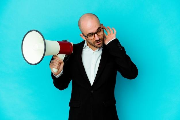 Młody biznes łysy mężczyzna trzyma megafon, próbując słuchać plotek.