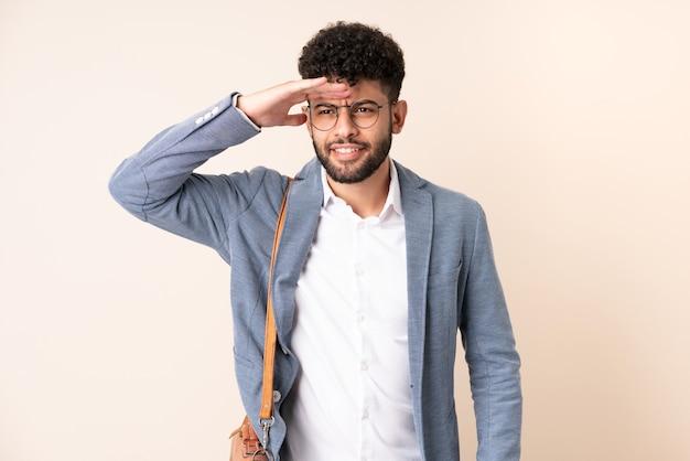 Młody biznes marokański mężczyzna na białym tle na beż, patrząc daleko ręką, aby coś spojrzeć