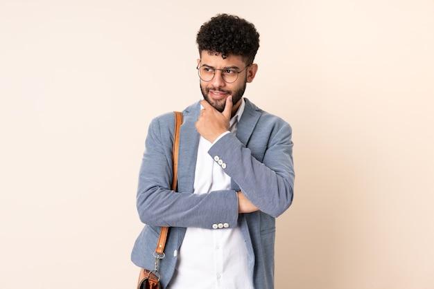 Młody biznes marokański mężczyzna na białym tle na beż, patrząc z boku