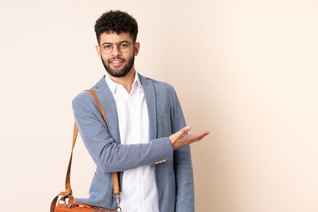 Młody biznes marokański mężczyzna na białym tle na beż przedstawiający pomysł, patrząc uśmiechnięty w kierunku