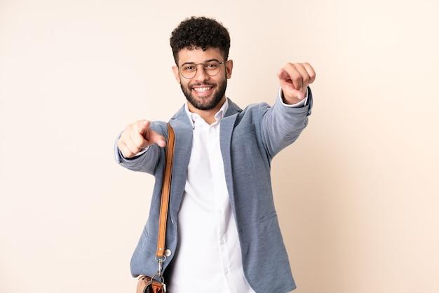 Młody biznes marokański mężczyzna na białym tle na beżowe punkty palcem na ciebie, uśmiechając się