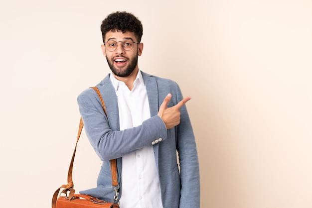 Młody biznes marokański mężczyzna na białym tle na beżowej ścianie zaskoczony i wskazujący bok