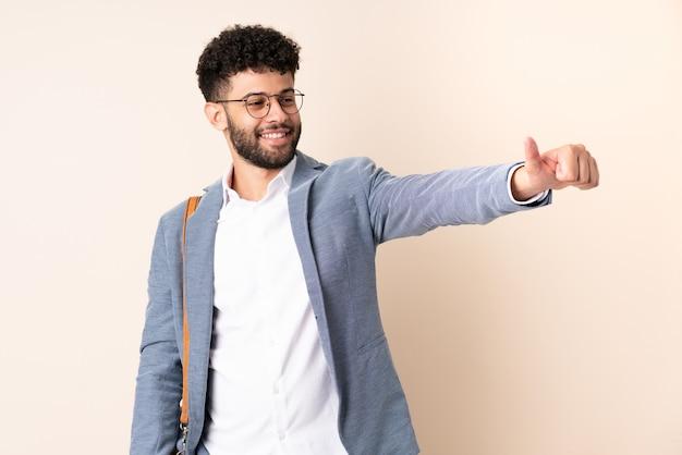 Młody biznes marokański mężczyzna na białym tle na beżowy, dając kciuki do góry gest