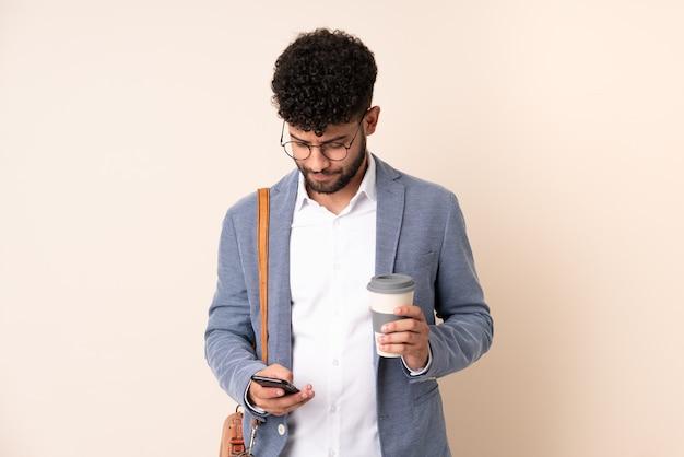 Młody biznes marokański mężczyzna na białym tle na beżowy trzymając kawę na wynos i telefon komórkowy