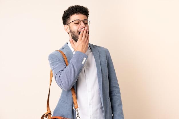 Młody biznes marokański mężczyzna na białym tle na beżowy ziewanie i stożek szeroko otwarte usta ręką