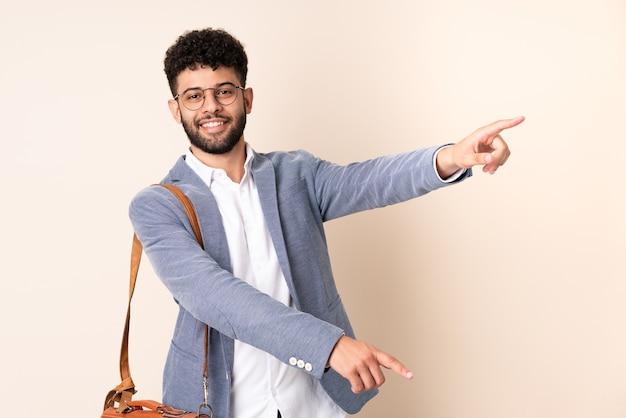 Młody biznes marokański mężczyzna na białym tle na beżowym palcu wskazującym z boku i przedstawia produkt