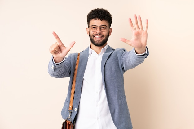 Młody biznes marokański mężczyzna na białym tle na beżu licząc siedem palcami