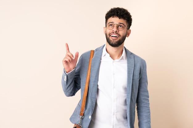 Młody biznes marokański mężczyzna na białym tle na beżu, wskazując w górę i zaskoczony