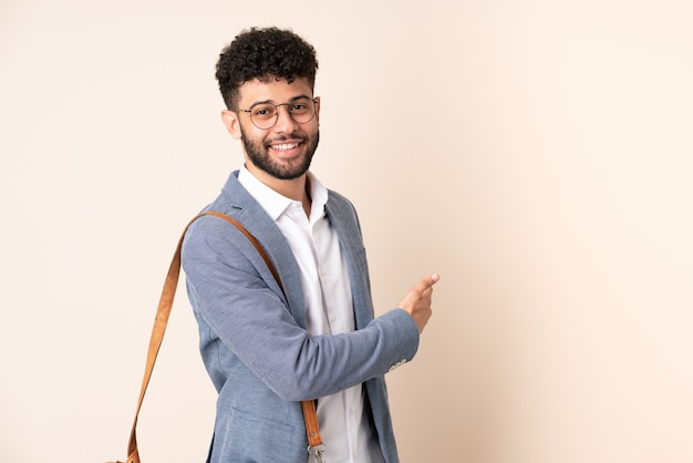 Młody biznes marokański mężczyzna na białym tle na beżu, wskazując wstecz
