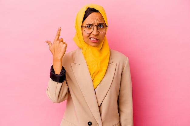 Młody biznes muzułmańska kobieta na białym tle na różowej ścianie pokazuje gest rozczarowania palcem wskazującym.