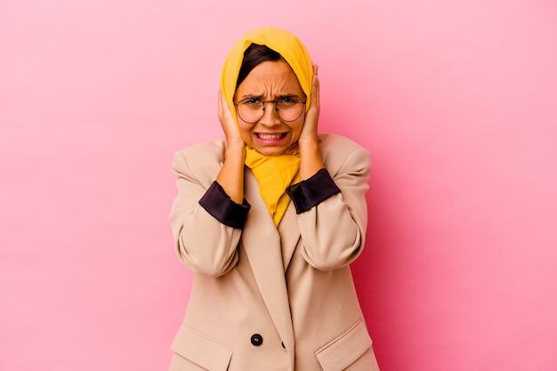 Młody biznes muzułmańska kobieta na białym tle na różowym tle obejmujące uszy rękami starając się nie słyszeć zbyt głośnego dźwięku.
