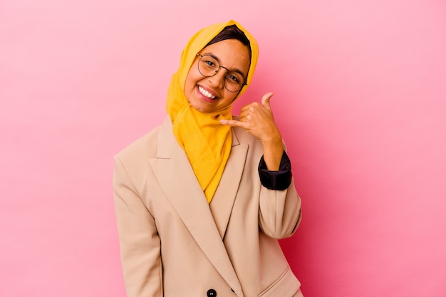 Młody biznes muzułmańska kobieta na białym tle na różowym tle pokazując gest połączenia z telefonu komórkowego palcami.