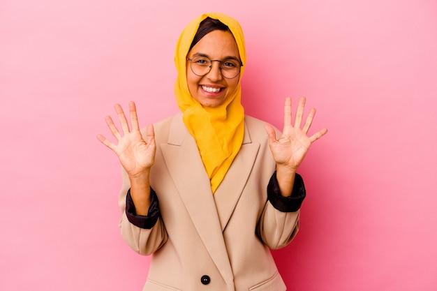 Młody biznes muzułmańska kobieta na białym tle na różowym tle pokazuje numer dziesięć rękami.
