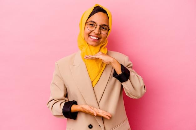 Młody biznes muzułmańska kobieta na białym tle na różowym tle, trzymając coś obiema rękami, prezentacja produktu.