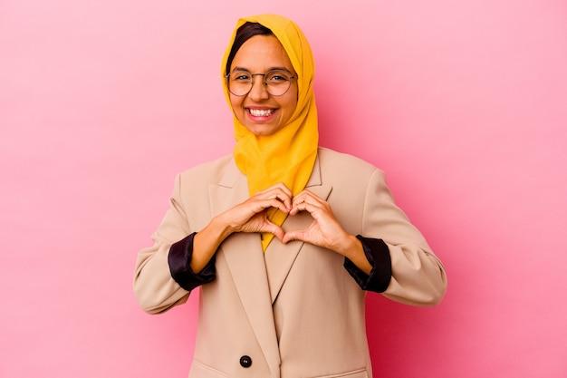 Młody biznes muzułmańska kobieta na białym tle na różowym tle, uśmiechając się i pokazując kształt serca rękami.