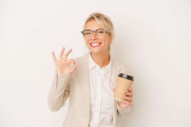 Młody biznes rosjanka gospodarstwa zabrać kawę na białym tle wesoły i pewny siebie, pokazując ok gest.