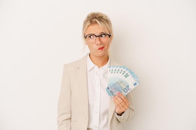 Młody biznes rosjanka trzyma banknoty na białym tle mylić, czuje się wątpliwa i niepewna.