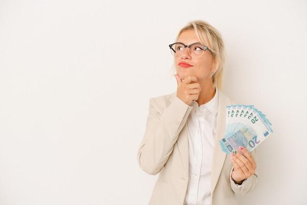 Młody biznes rosjanka trzyma banknoty na białym tle patrząc w bok z wątpliwym i sceptycznym wyrazem.