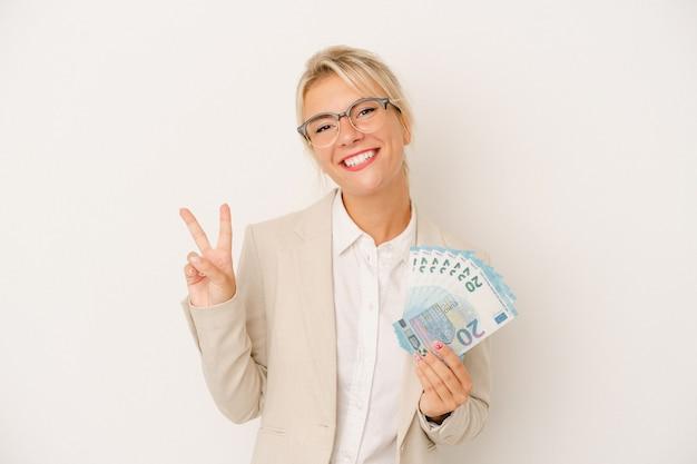 Młody biznes rosjanka trzyma banknoty na białym tle pokazując numer dwa palcami.
