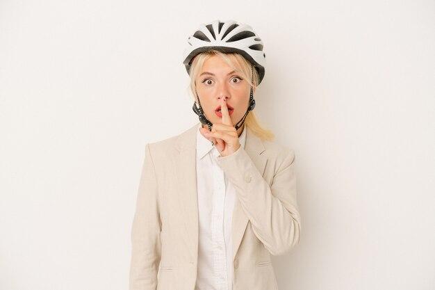 Młody biznes rosjanka trzyma kask rowerowy na białym tle dochowując tajemnicy lub prosząc o ciszę.