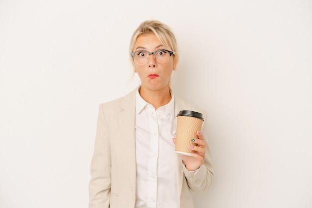 Młody biznes rosjanka trzyma na wynos kawę na białym tle wzrusza ramionami i otwiera oczy zdezorientowany.
