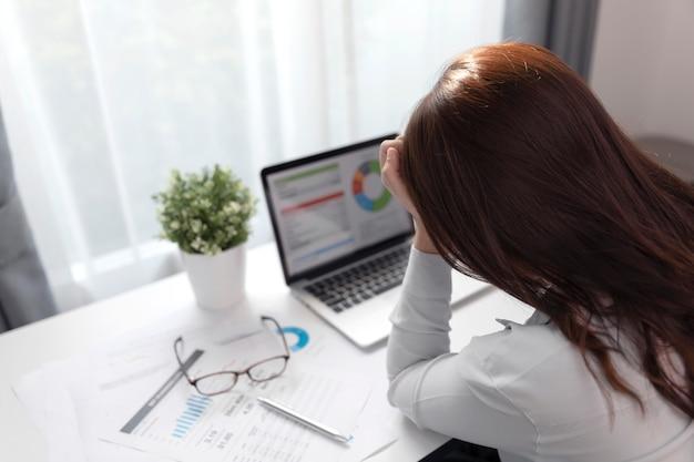 Młody biznes sfrustowana kobieta pracuje przy biurowym biurkiem przed laptopem cierpi od czoła