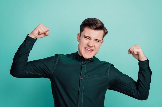 Młody biznes sukces triumf człowieka pokaż triceps mięśni ramienia na białym tle na turkusowym tle