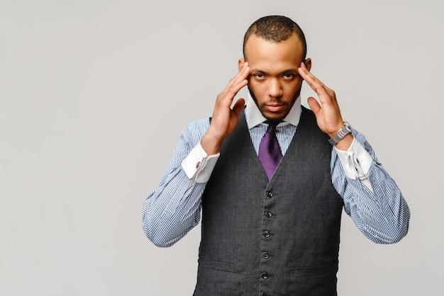 Młody biznesmen afro amerykański, dotykając głowy z powodu bólu głowy i stresu.