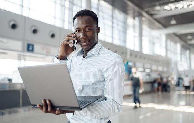 Młody biznesmen afro z laptopa i telefonu w salonie samochodowym. sukcesy biznesmena na motor show, murzyn w wizytowym