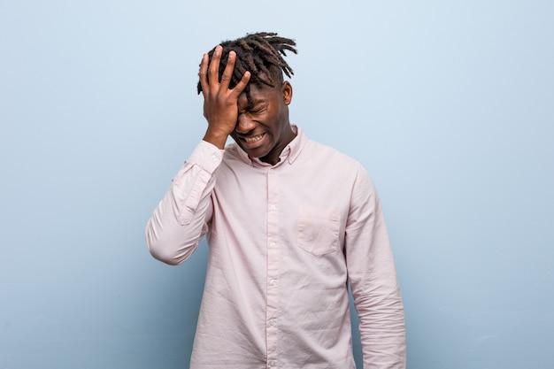 Młody biznesmen afrykański czarny człowiek zapominając coś, uderzając czoło dłonią i zamykając oczy.