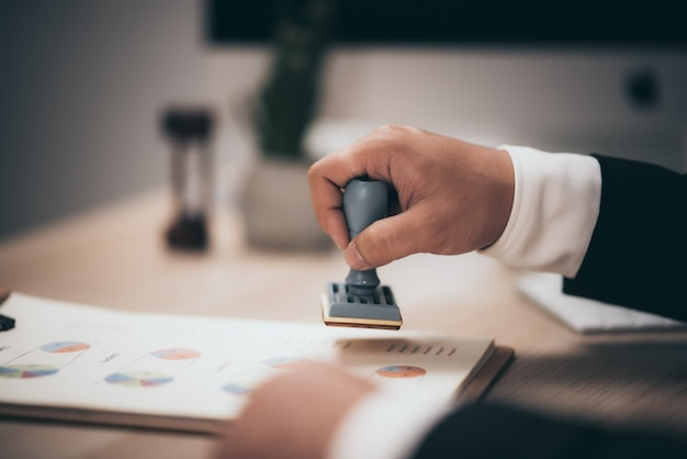 Młody biznesmen aprobujący stempel stempel na papierze umowy biznesowej, zatwierdzone pieniądze pożyczki.