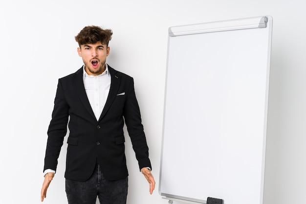 Młody biznesmen arabski coaching biznesowy krzyczy bardzo zły i agresywny.