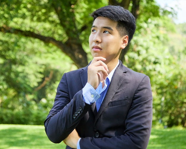 Młody biznesmen azjatyckich relaks w parku przyrody